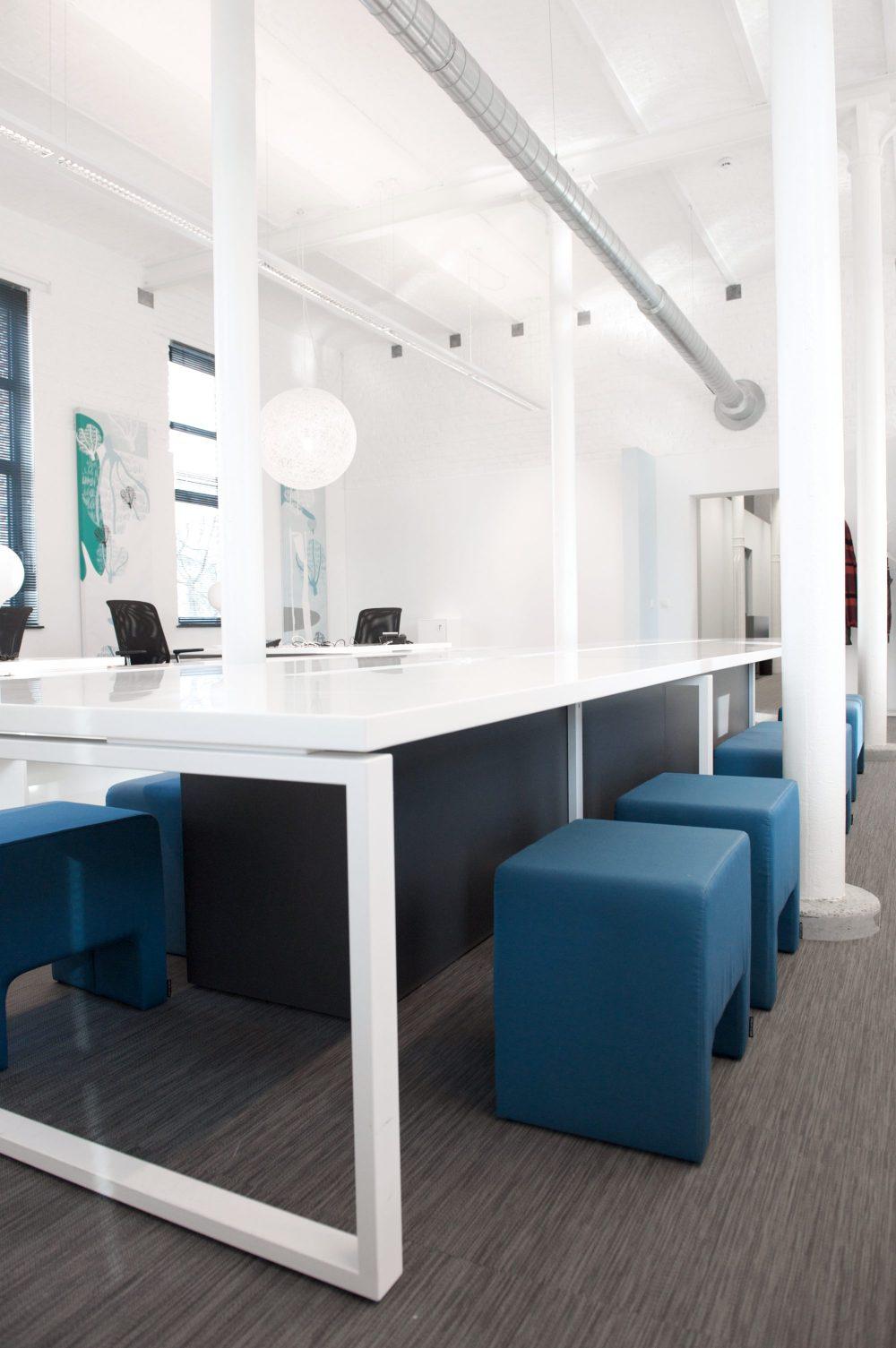 espace bureaux toute blanche, bureaux et mobilier blancs, sièges bureaux noirstable blanc, poufs bleus