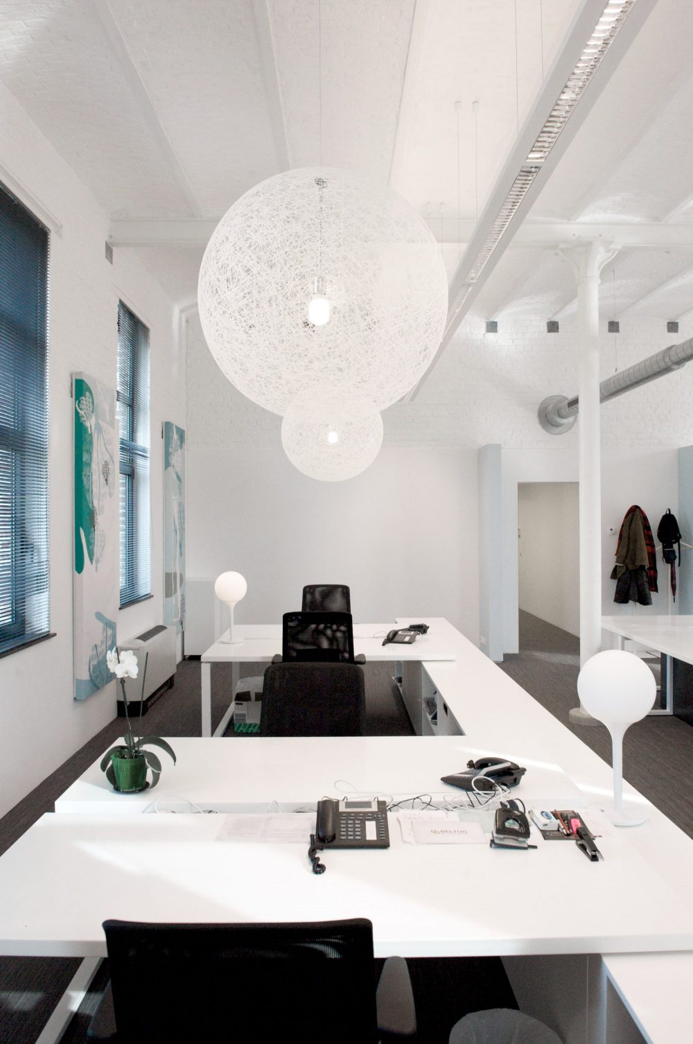 tables blanches, chaises bureaux noirs, lampes boules blanches