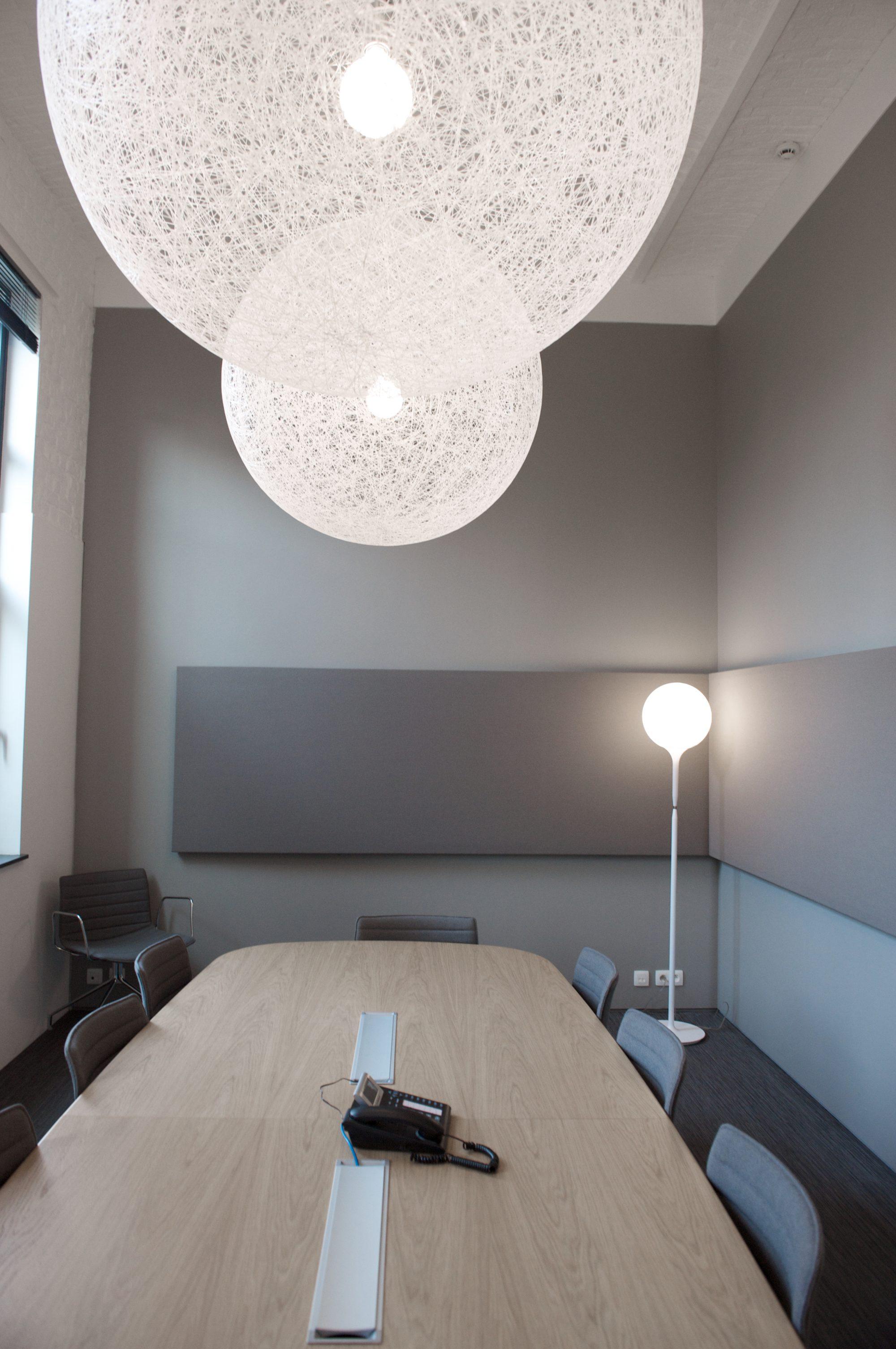 vergadertafel hout, grijs-beige muur, akoestische panelen, witte lampen