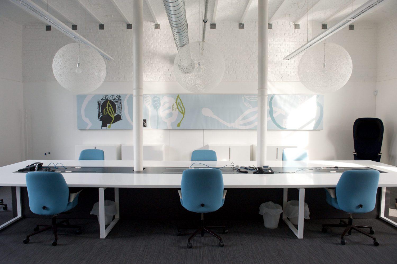 grande table blanche, sol gris, chaises bleus