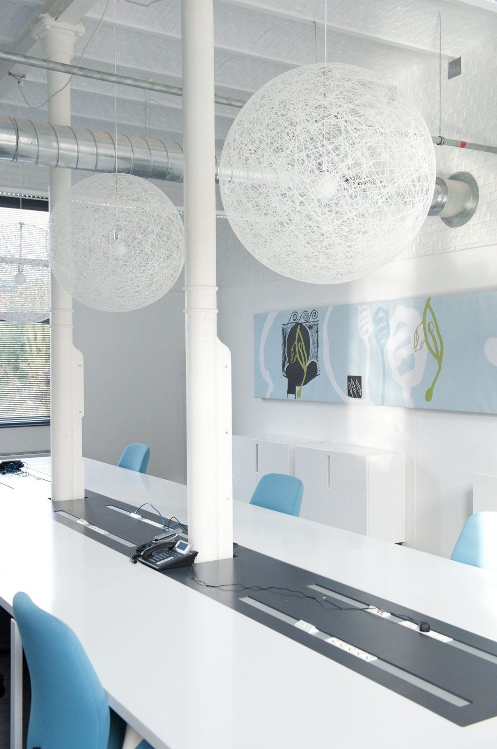 grand bureau blanc pour travail équipe, sièges bleus, lampes boules blanches