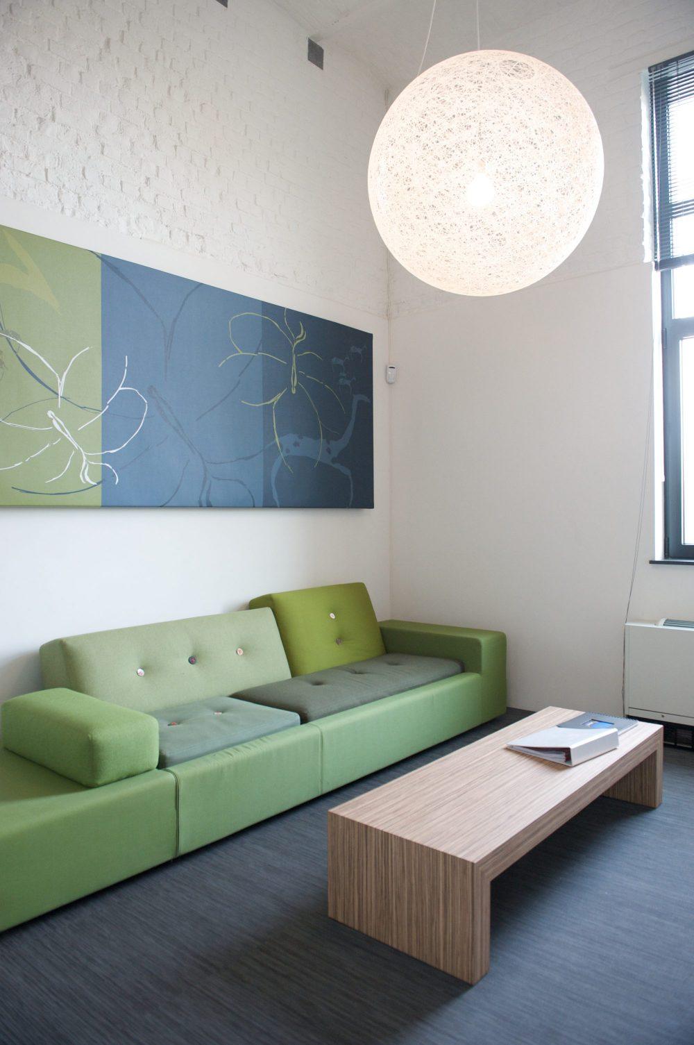 sofa vert, oeuvre d'art tons vert et bleux, table basse en bois