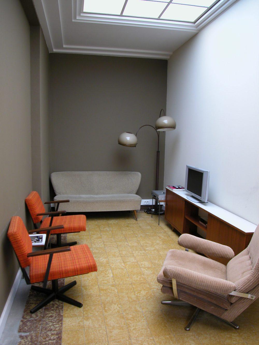 vintage salon, grijze muren, oude tegelvloer, vintage lamp