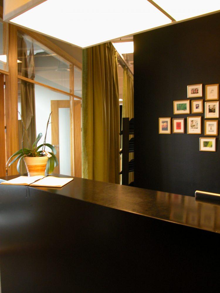 comptoir d'accueil noir, mur noir avec petits cadres, rideaux verts