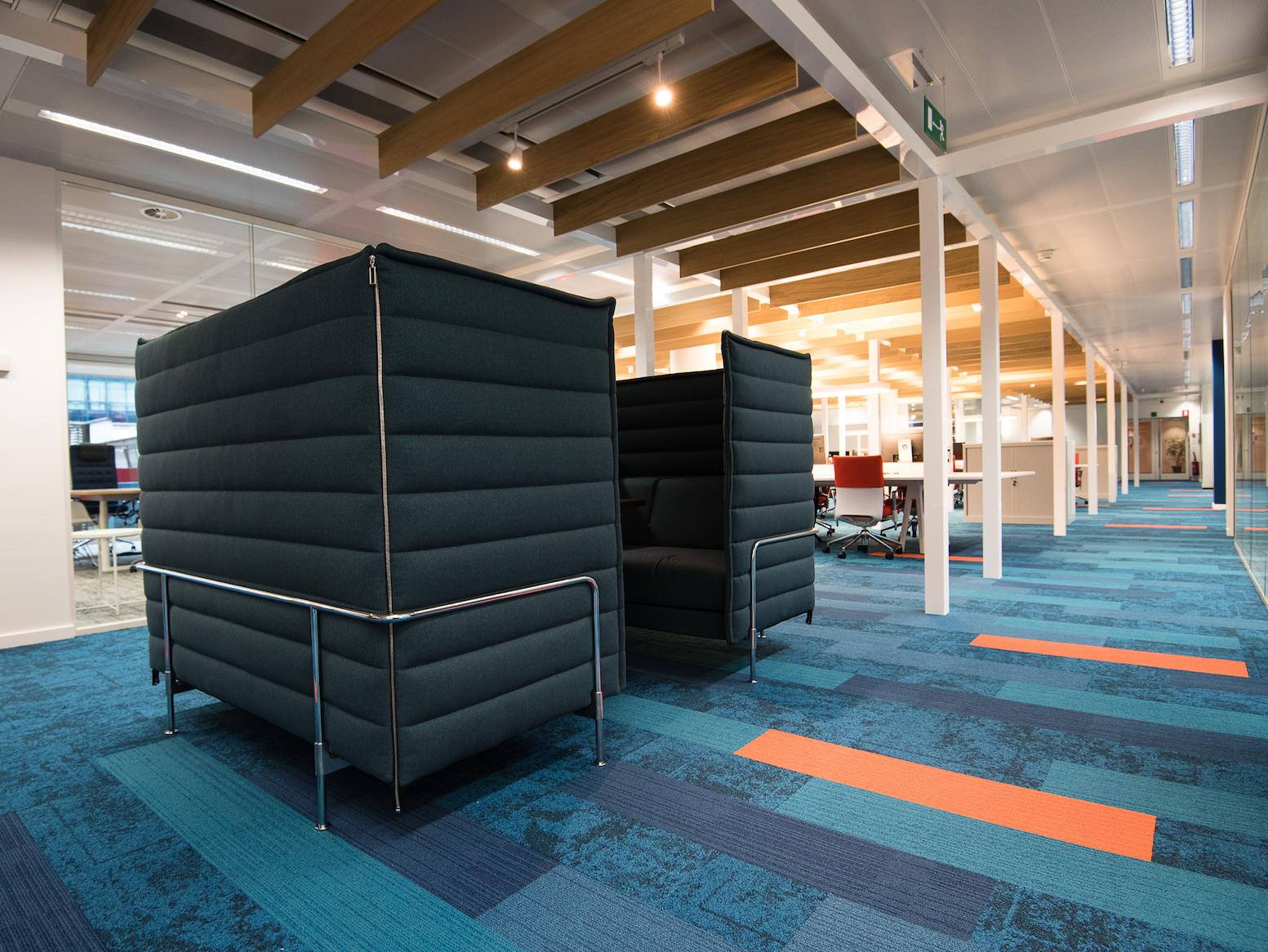 Blauw tapijt met oranje accenten, baluwe werk-alcove en uitzicht kantoor