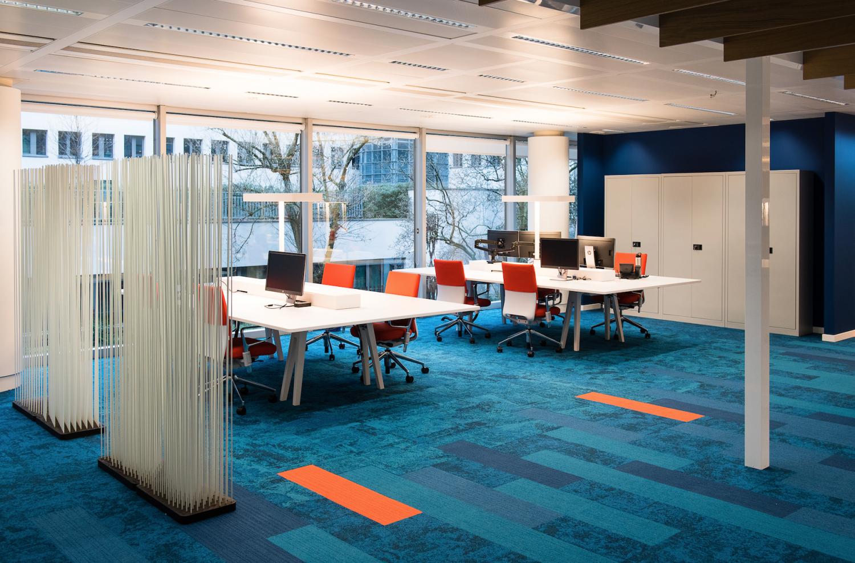 Tapis bleu et details oranges, bureaux blancs, sièges oranges