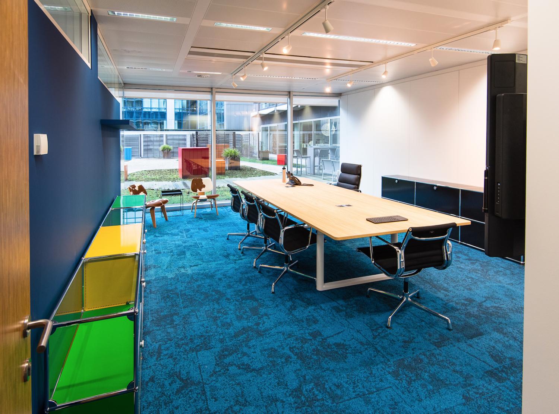 Espace de réunion, table en bois, mur bleu, tapis bleu