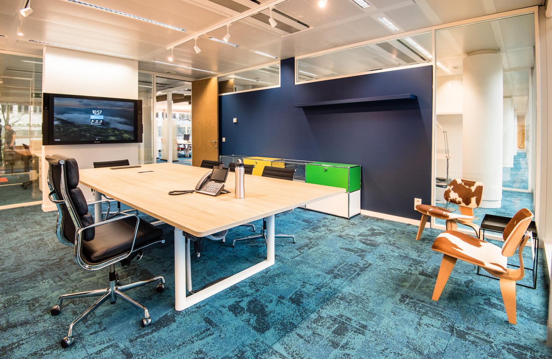 tapis bleu, table de réunion-bureau, sièges Vitra