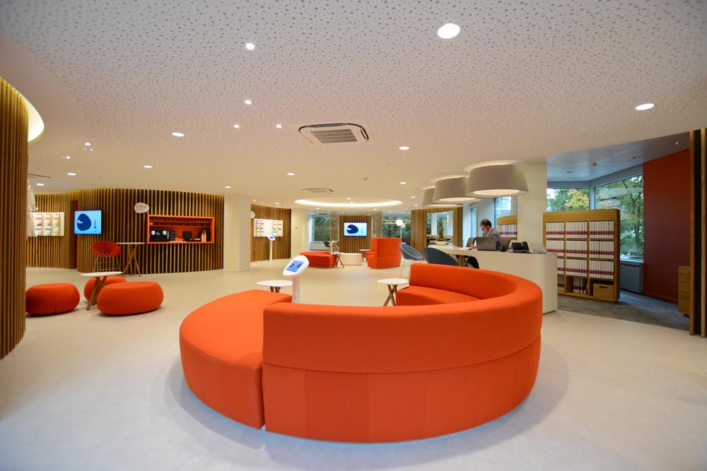 salon d'attente ethias woluwe, meubles oranges, sol blanc, claustra bois