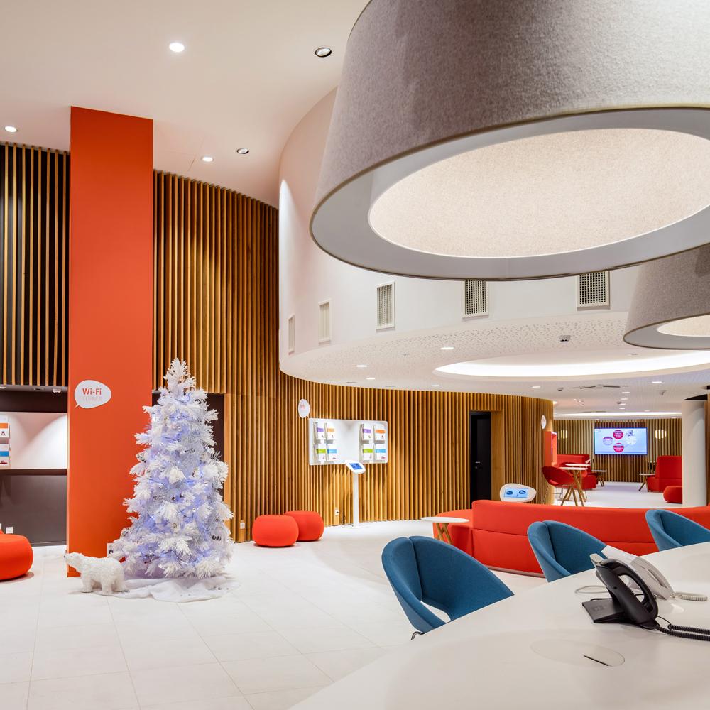witte vloer, witte kerstboom, houten claustra gebigen wand, oranje pilaar
