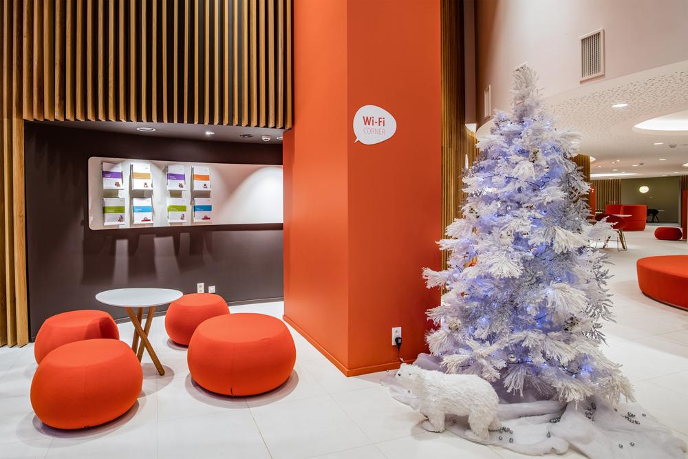 Oranje pillaar, zitpoefjes oranje, witte vloer, een kerstboom