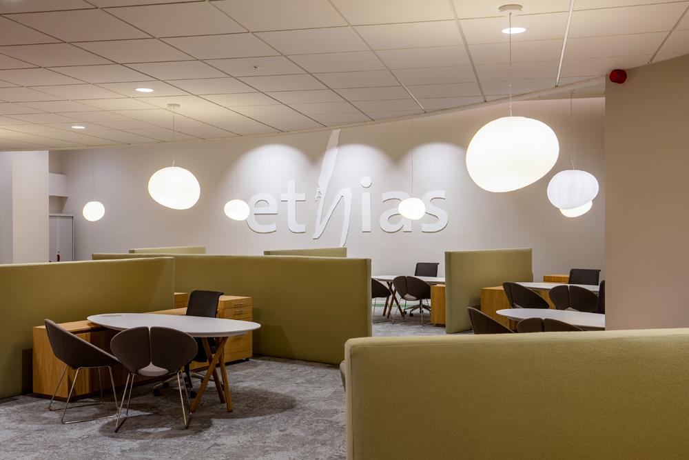 Grijsbeige muur met logo ethias, akoestische paravents in groen vilt, grijs tapijt