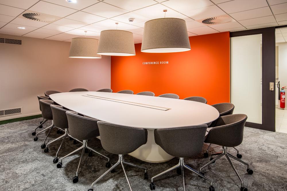 Vergaderruimte met witte vergadertafel en oranje muur