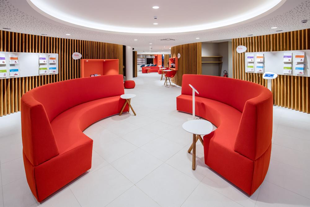 Open ruimte met witte vloer en 2 oranje zetels in cirkel