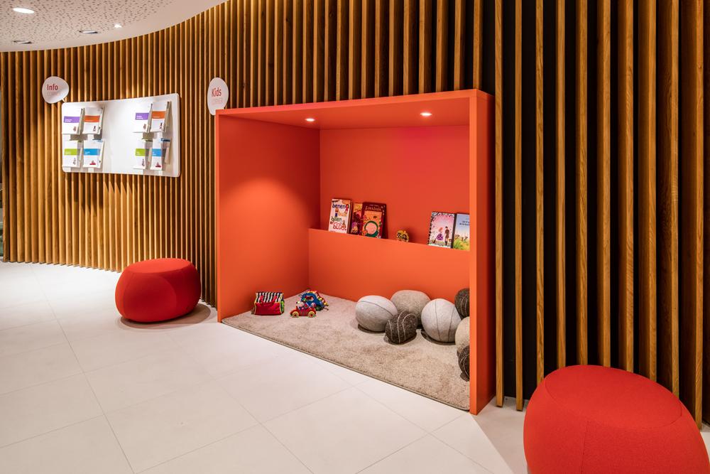 Kinderhoek oranje, houten gebogen lattenwand, witte vloer