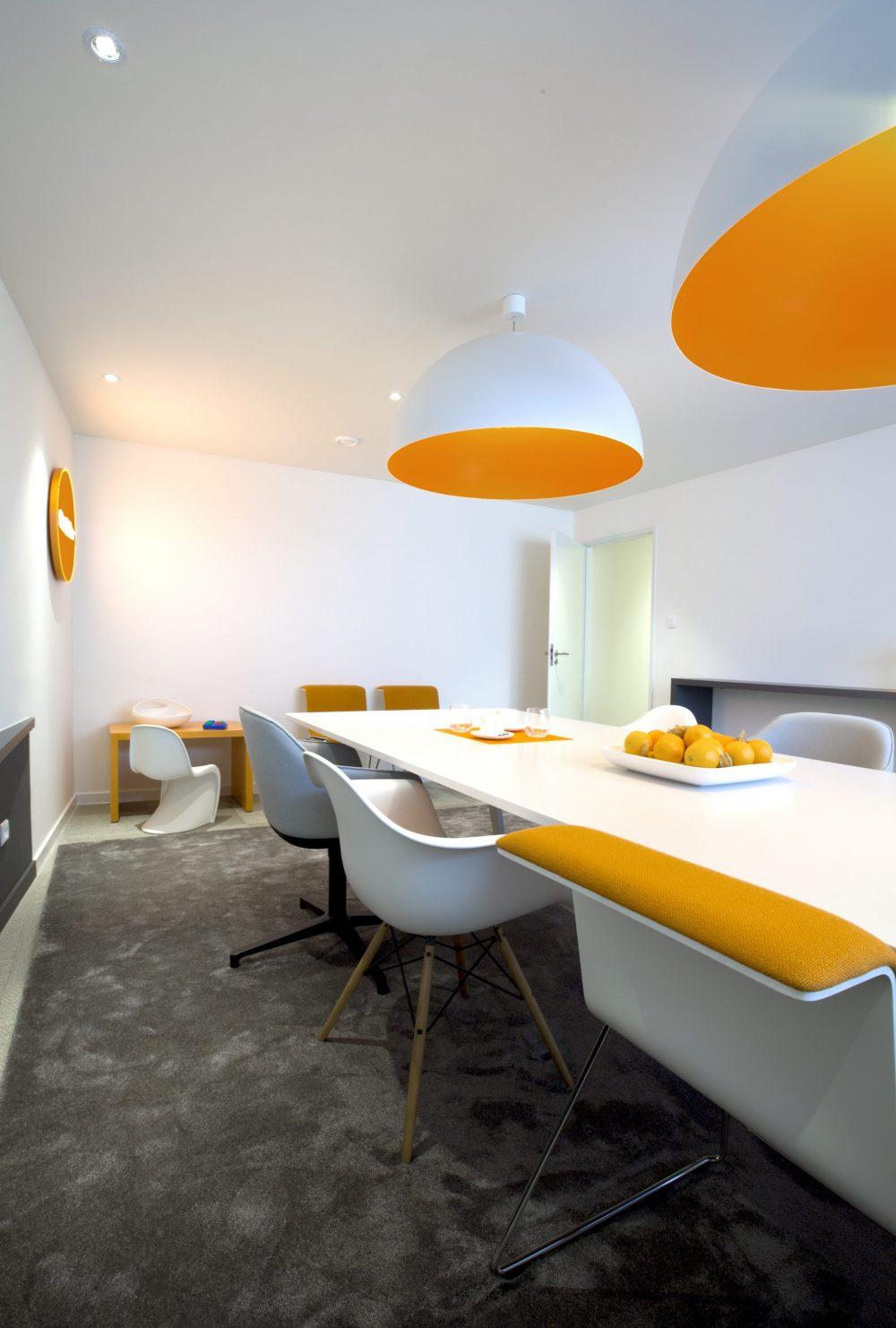 espace de réunion, tapis gris, meubles orange et blanc