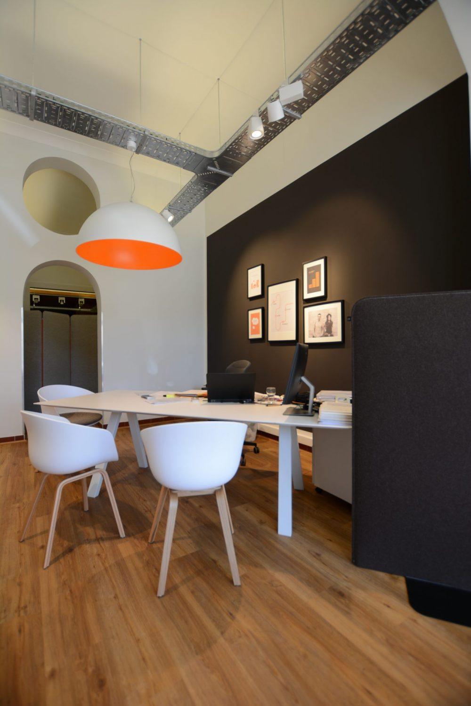 Bureau met witte stoelen en zwarte muur