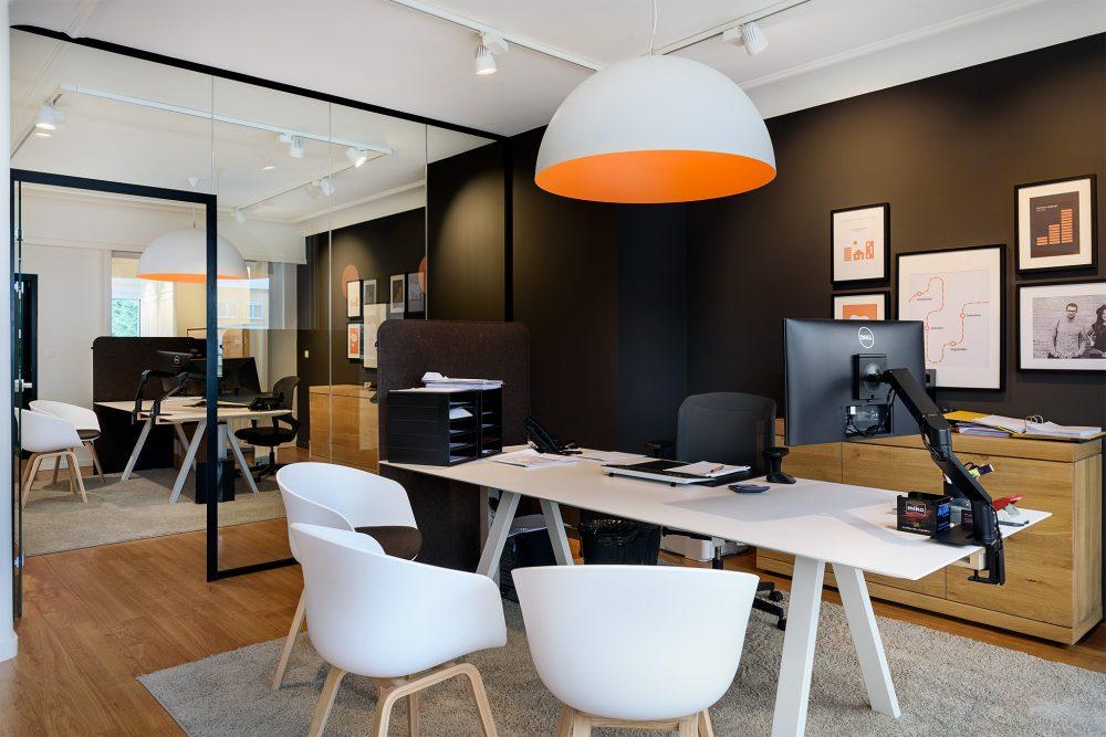 bureau oranje lamp en witte stoelen