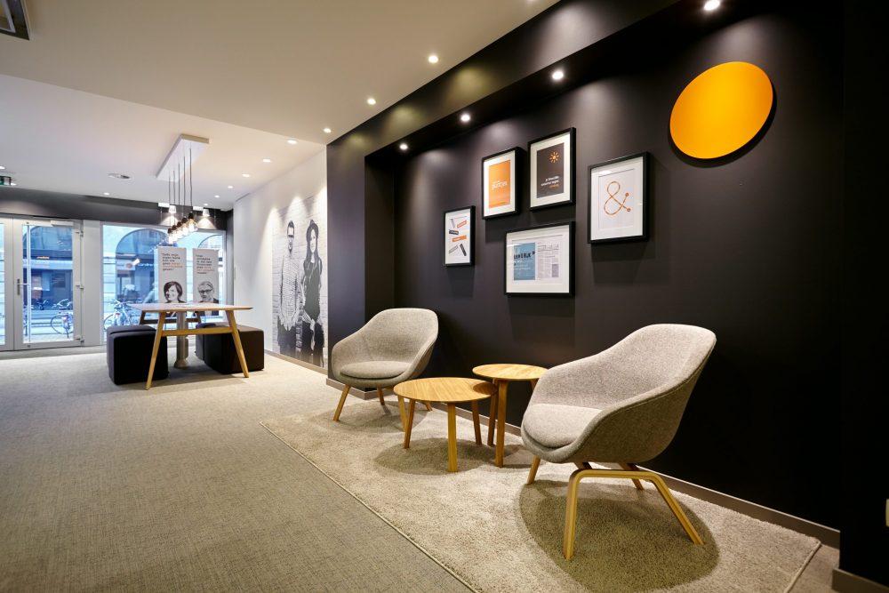 mur brun, cadres noirs, sièges lounge