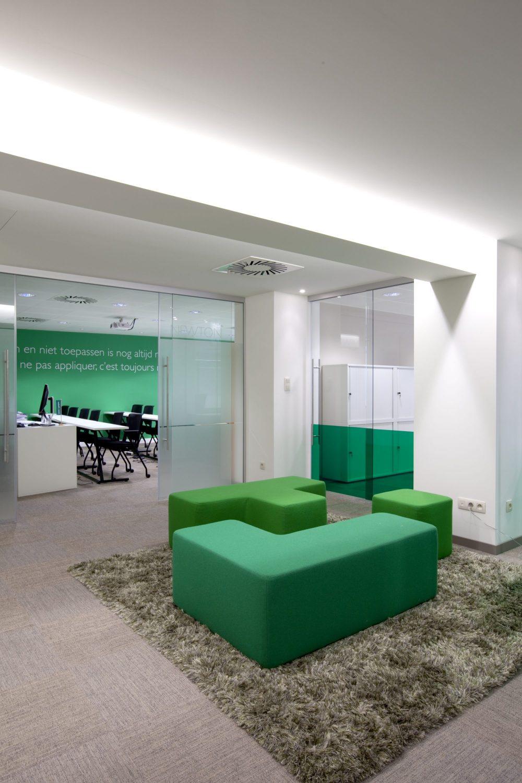 poufs verts carrés, tapis vert, murs blancs et verts, chaises noirs, portes en verre
