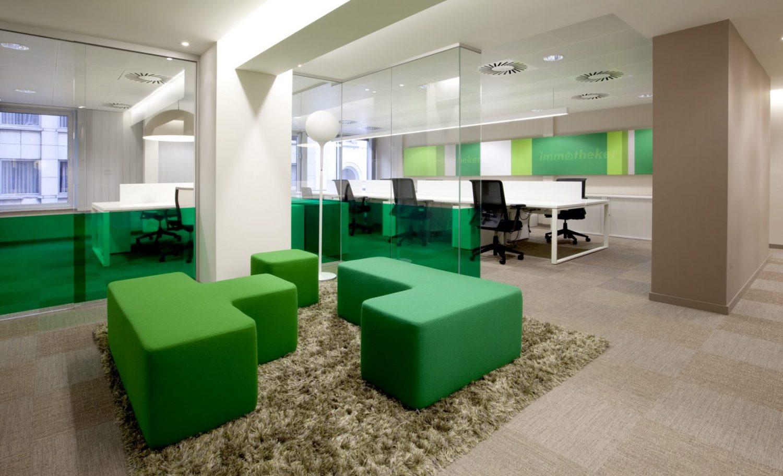 poufs verts carrés, tapis vert, mur beige-gris, bureaux blancs