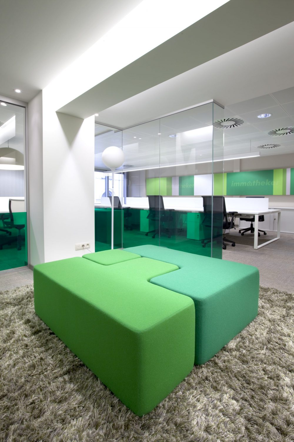 Green carpet, green sitting elements in fabric, workspace, logo Immotheker on wall