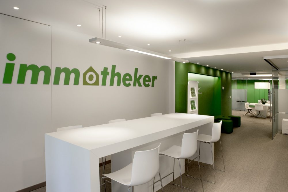 Logo Immotheker on white wall, white bar table, green walls
