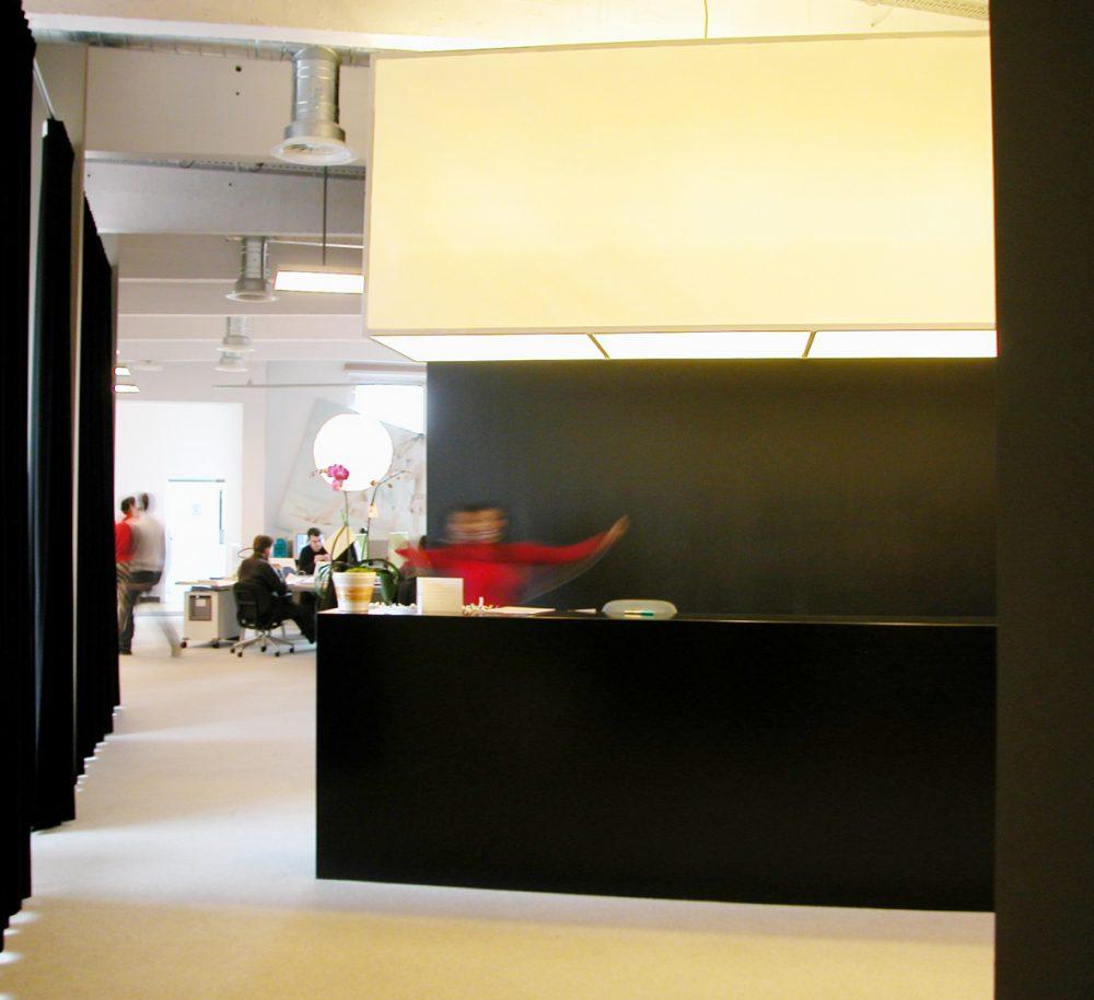 comptoir d'accueil noir, mur noir, grande suspension lumineuse, rideaux noirs
