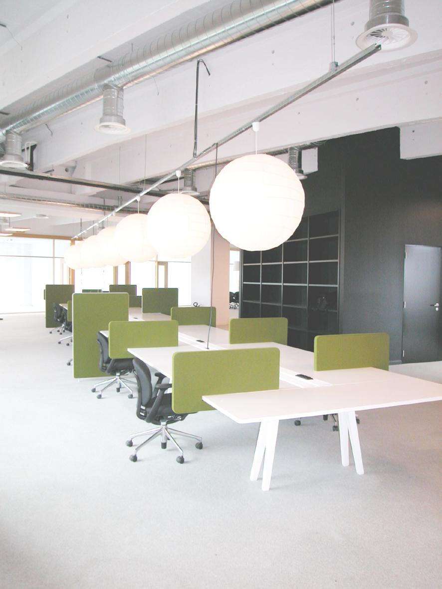 Lange witte tafel met groene scheidingen, zwarte muur