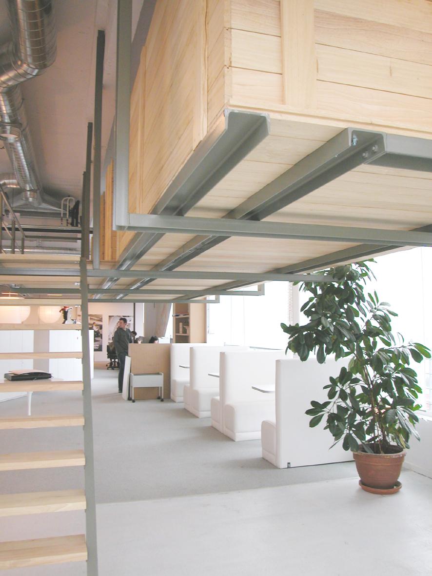 Bankjes wit achter elkaar en grote plant, houten constructie