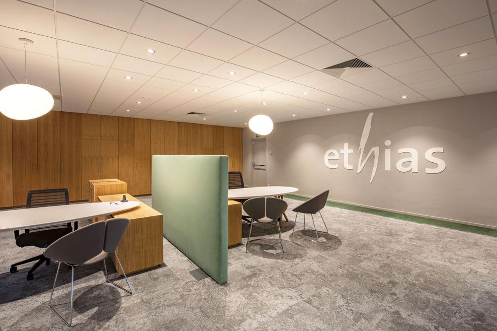 tapis gris, mur gris avec logo ethias en blanc, armoires en bois, bureaux blancs
