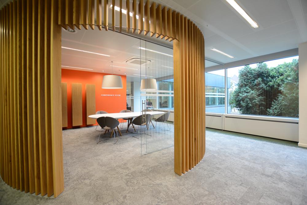 tapis gris, claustra en bois, mur orange, table blanche, sièges gris