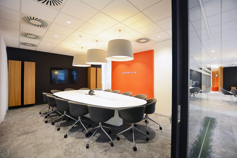 witte vergadertafel in organische vorm, grijze stoelen, oranje muur, zwarte muur