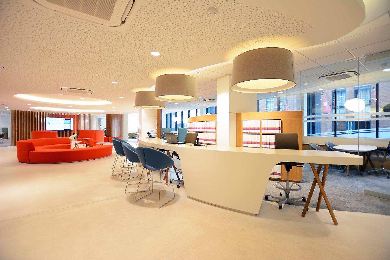 witte vloer en onthaaldesk, oranje ronde sofa, wit plafond met gaatjes