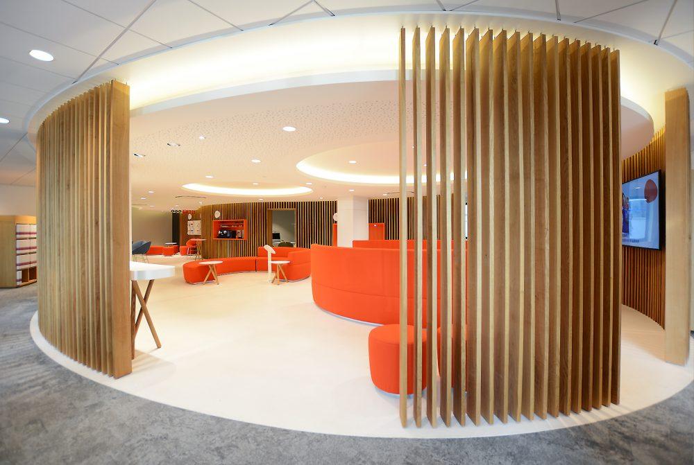 wooden slads in round waiting area, orange furniture