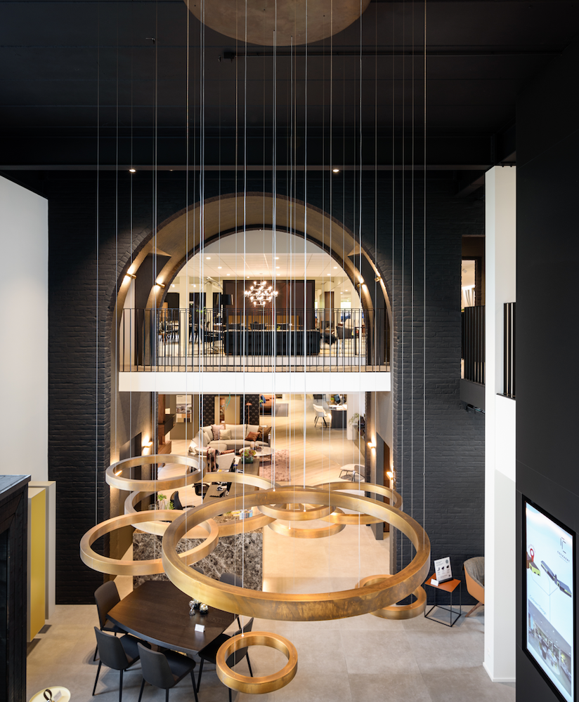 showroom design furniture, black walls, brass lighting rings