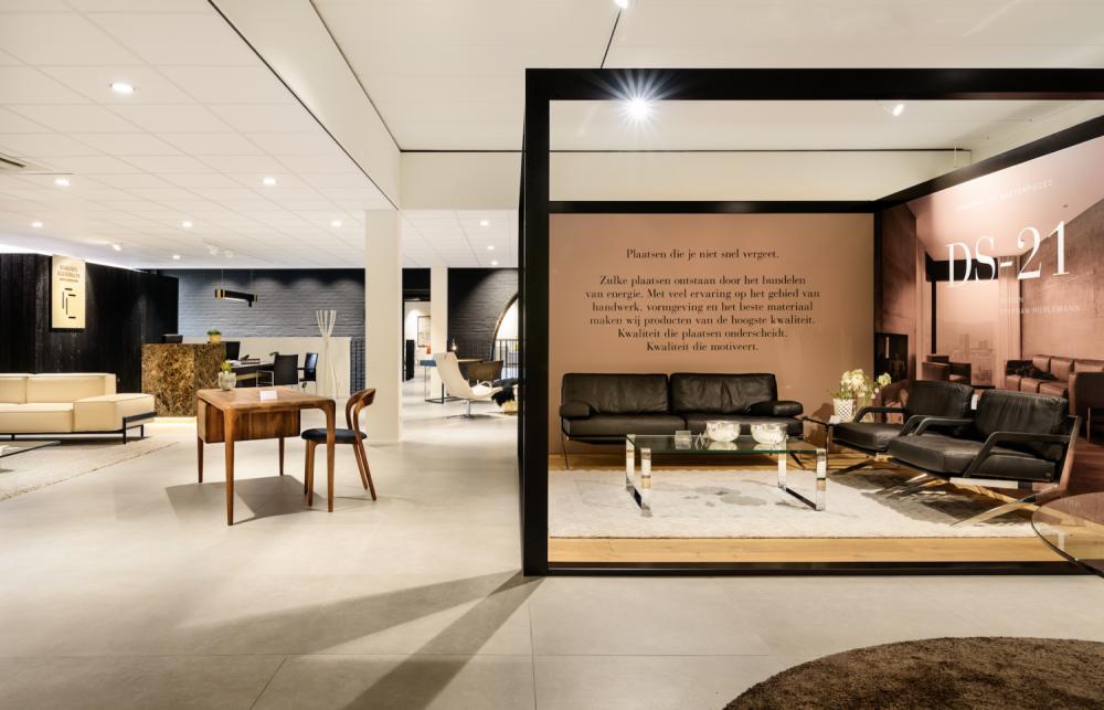 showroom design meubelen, cadre noir, plafond blanc, sol gris clair, bureau en bois