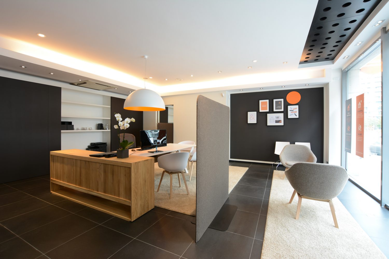 black floor, beige carpet, wooden cuboard, darkbrown wall with frames