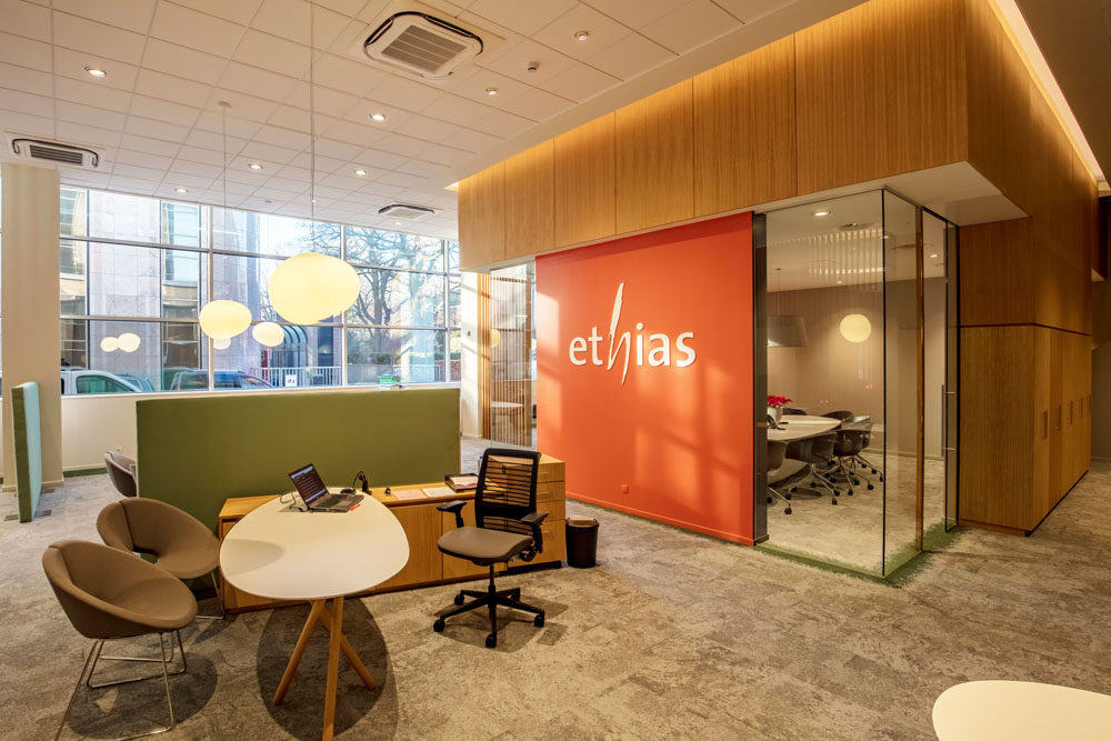 orange wall, logo ethias, green separation element, white organic office tables