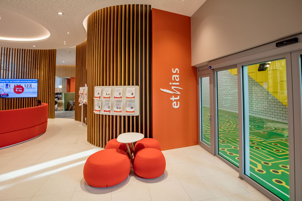 logo ethias, orange walls, wooden claustra, sitting cushions