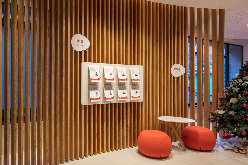 claustra en bois, display brochures, poufs oranges